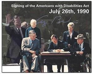 President George H. W. Bush is sitting at a table siging the Americans with Disabilities Act.