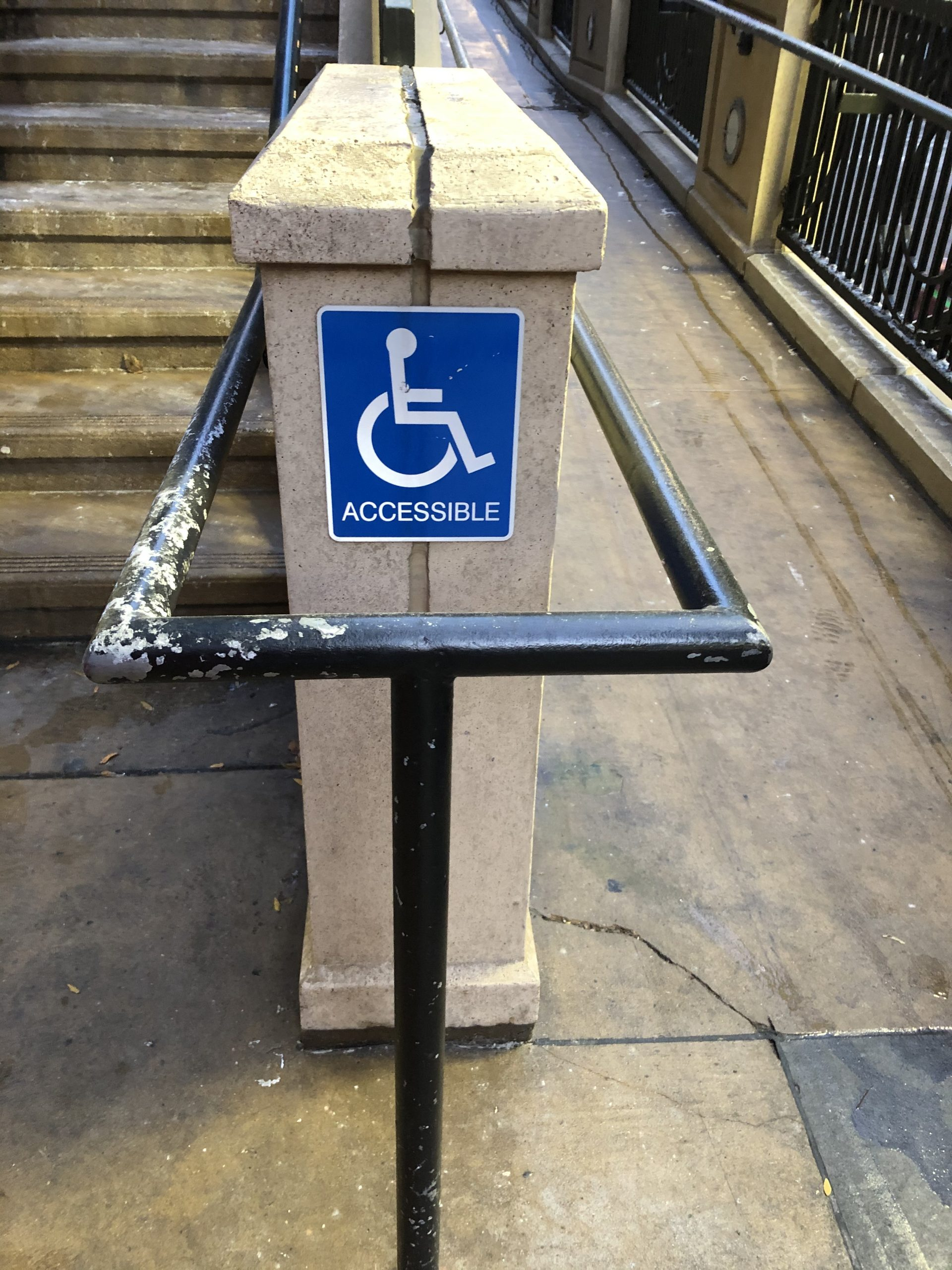 photo of ramp and blue sign with wheelchair accessibility symbol