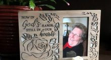 "photo of smiling woman with impishly tilted head in wooden frame that says ""Now in God's hands, still in our hearts"""