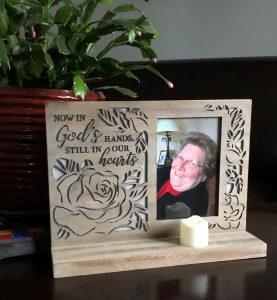 """photo of smiling woman with impishly tilted head in wooden frame that says """"Now in God's hands, still in our hearts"""""""