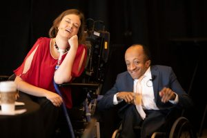 A white woman with shoulder length brown hair, wearing a rad blouse, using a wheelchair and a ventilator, sitting beside am African American man wearing a dark suit and pink tie. Both look happy and excited.