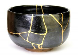 dark grey, glazed pottery bowl with think veins of gold where cracks had been mended