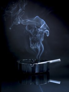 smouldering cigarette in an ashtray, with smoke wafting upwards