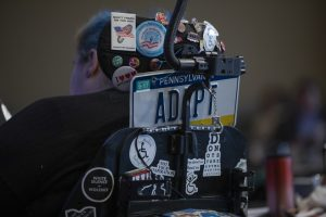 Photo of a disability rights activist in a wheelchair, taken from the back. A license plate saying ADAPT and a number of disability rights buttons are visible