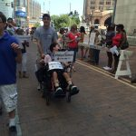 Student in a wheelchair holding #IWantToWork sign